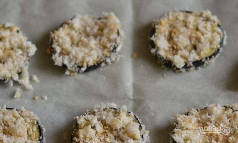 Выложите баклажаны в панировке на противень, застеленный пергаментом. Поставьте в духовку, разогретую до ста девяноста градусов, и запекайте двенадцать-пятнадцать минут.