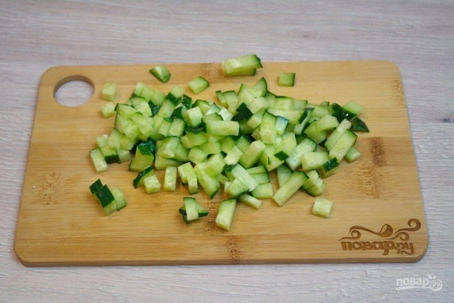 4. Свежий огурец нарежьте небольшими кубиками. Если у вас перезревший огурчик, удалите предварительно семена и только потом нарежьте огурец для салата. Крупные семена портят салат.