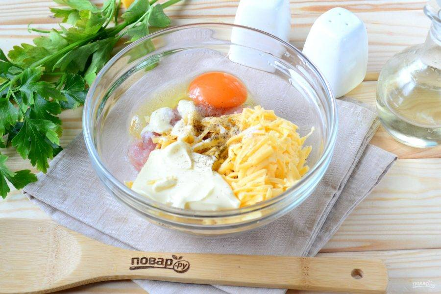 Добавьте к грудке натертый на крупной терке сыр, яйцо, майонез, посолите и поперчите по вкусу. Хорошенько перемешайте массу. Теперь добавьте ½ ст. ложки муки, снова перемешайте. Если масса останется жидковатой, то добавьте еще ½ ст. ложки муки. Разное количество муки может зависеть от жидкости майонеза (или сметаны) и размера яйца.