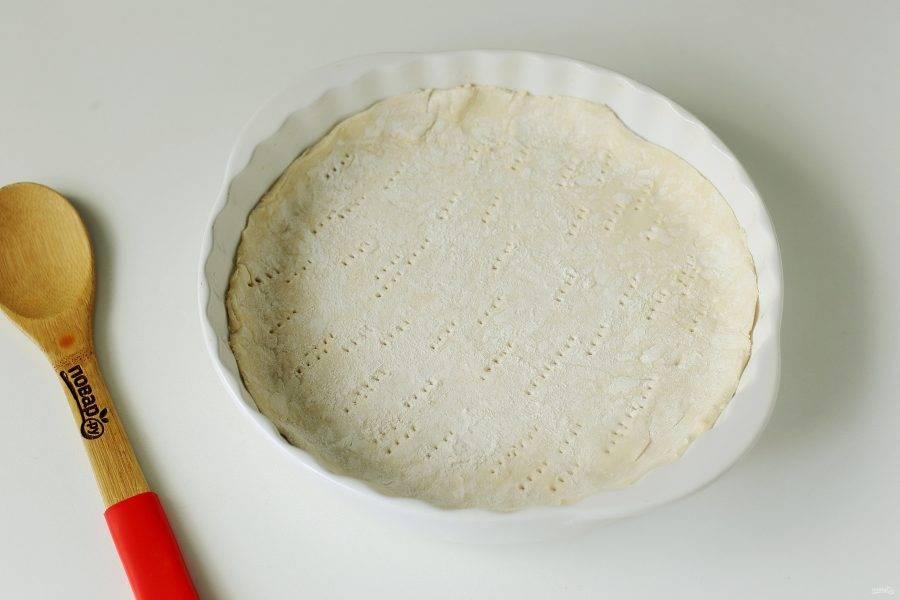 Форму для выпечки смажьте маслом. Тесто раскатайте по размеру формы, аккуратно перенесите, сформируйте руками небольшие бортики и наколите дно вилкой.