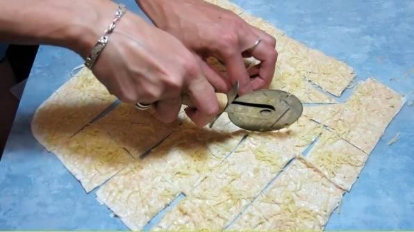 5. Выкладываем лаваш на противень (предварительно смажьте его растительным маслом и застелите пергаментом). Теперь посыпаем тертым сыром и нарезаем специальным ножом.