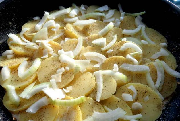 Лук нарезаем полукольцами и выкладываем на картофель.