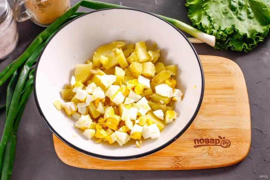 Очистите куриное яйцо и картофель от скорлупы, кожуры, промойте в воде. Нарежьте средними или мелкими кубиками и высыпьте обе нарезки в глубокую емкость.