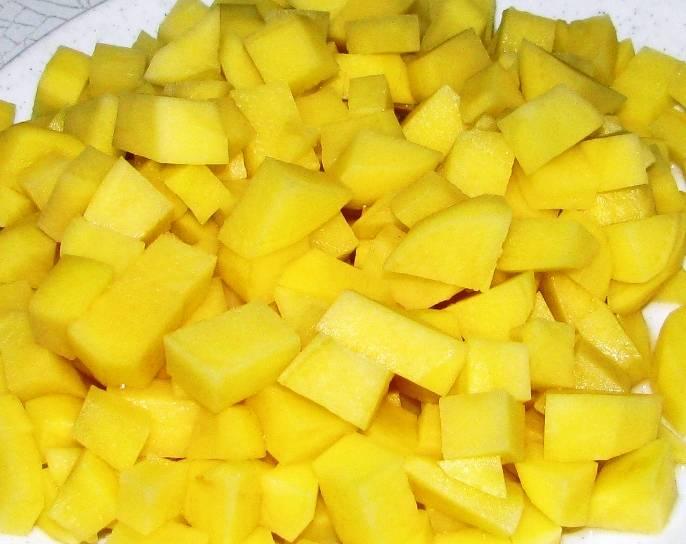 Картофель порежьте кубиками и бросьте в кастрюлю к гороху.