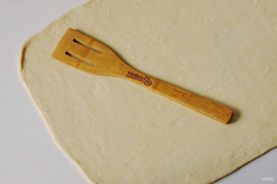 Когда тесто подойдет, разделите его на две части. Каждую раскатайте в прямоугольный тонкий пласт.