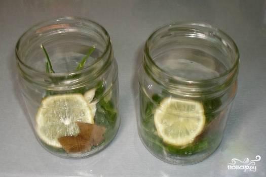 Тщательно промываем в прохладной воде огурцы, зелень и лимон. На дно стерилизованных банок укладываем листик хрена, пару веточек укропа, дольку лимона, лаврушку и душистый перец.