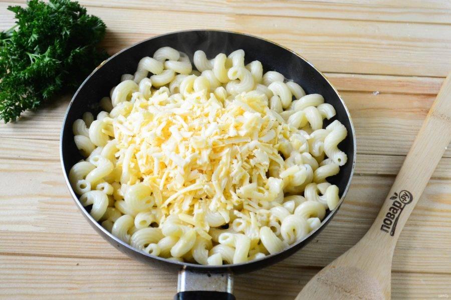 Макароны откиньте на дуршлаг, а затем переложите в сковороду с разогретым растительным маслом. Туда же добавьте натертый на крупной терке твердый сыр и прогревайте несколько минут, часто помешивая, чтобы сыр расплавился и максимально распределился в макаронах.