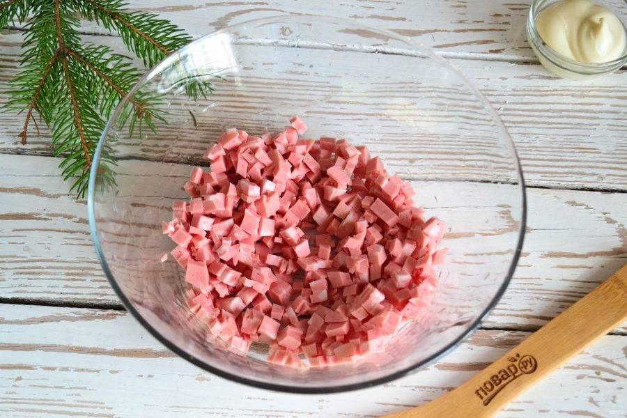 Вареную колбасу нарежьте мелким кубиком.