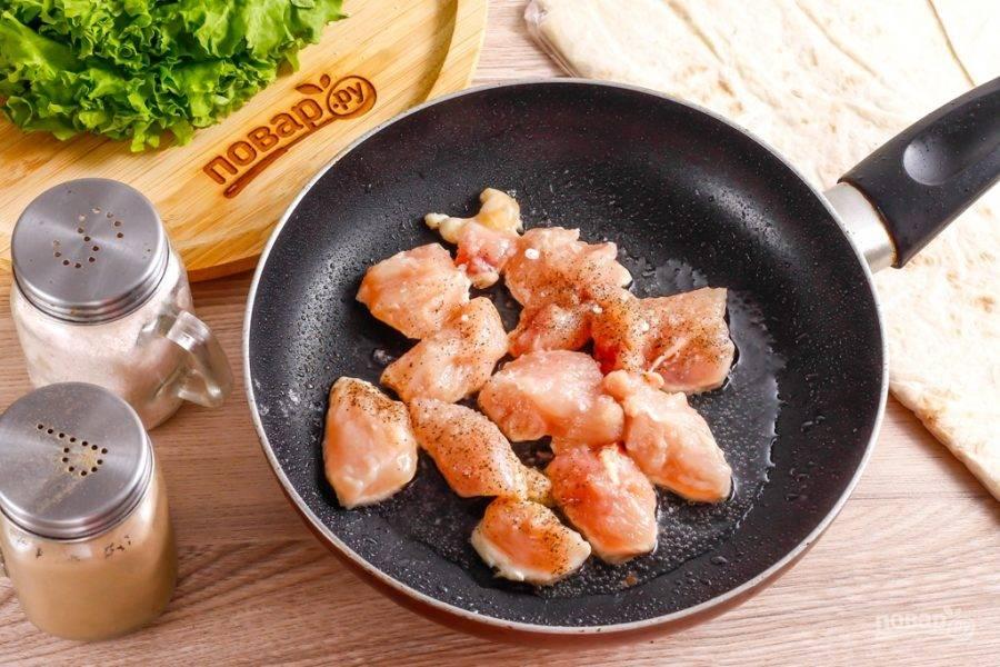 Куриное филе промойте в воде и обсушите его бумажными салфетками. Можно использовать любую часть куриного мяса, например — срезанную с бедрышек или голеней. Срежьте жилы и пленки, нарежьте кубиками и выложите на сковороду, прогрев на ней растительное масло.