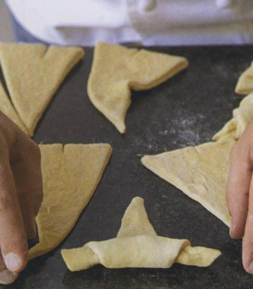 3. Далее аккуратно сверните треугольники к меньшему краю, как бы наматывая тесто.