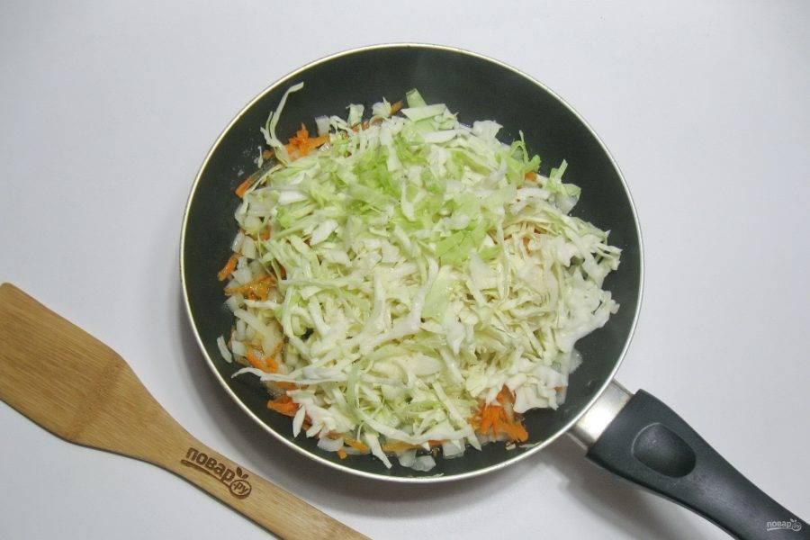 Морковь очистите, помойте и натрите на терке. Капусту нашинкуйте тонкой соломкой. Морковь и капусту выложите в сковороду к луку.