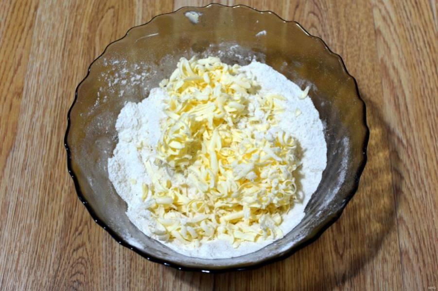 Смешайте просеянную с разрыхлителем муку с солью и сахаром. Сверху на смесь натрите замороженное сливочное масло (на крупной терке). Руками быстро смешайте все ингредиенты в крошку, стараясь не давать маслу таять.