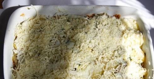 Смазать оставшимся соусом бешамель, посыпать тёртым сыром.