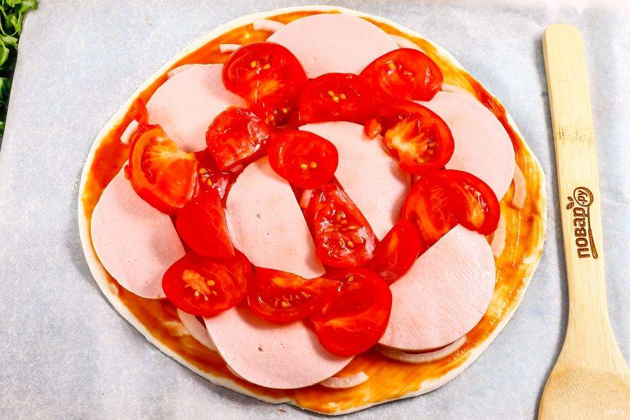 Промойте помидоры и нарежьте их слайсами, вырезая зеленые сердцевинки. Выложите на основу.
