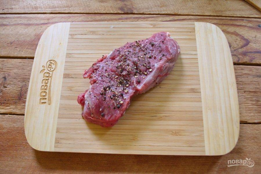 Со всех сторон посыпьте стейк черным дробленым перцем и солью.