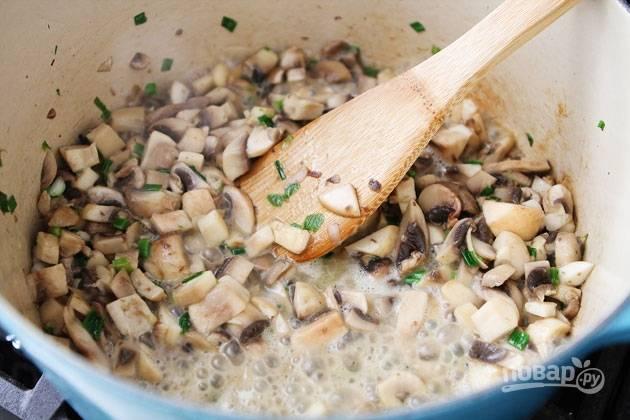 2.Растопите в кастрюле сливочное масло, выложите все разом: грибы и зеленый лук. Обжаривайте до испарения жидкости.