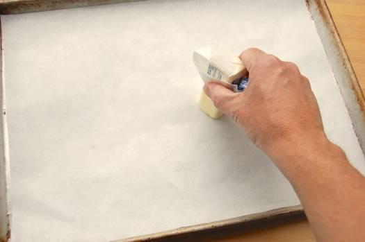 5. Отправить сотейник на огонь. Тем временем подготовить противень, застелив его пергаментом для выпечки. Кусочком сливочного масла как следует промазать пергамент. В рецепт приготовления яблок в красной карамели можно использовать также силиконовый коврик, например.