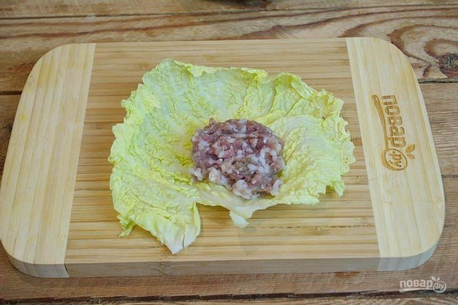 3. Лист капусты выложите на стол. На серединку выложите жменьку подготовленного фарша.