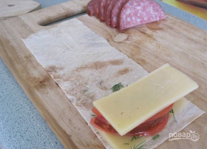 На край полоски лаваша выкладываем ингредиенты в такой последовательности: cыр - помидор - колбаса - помидор - сыр.