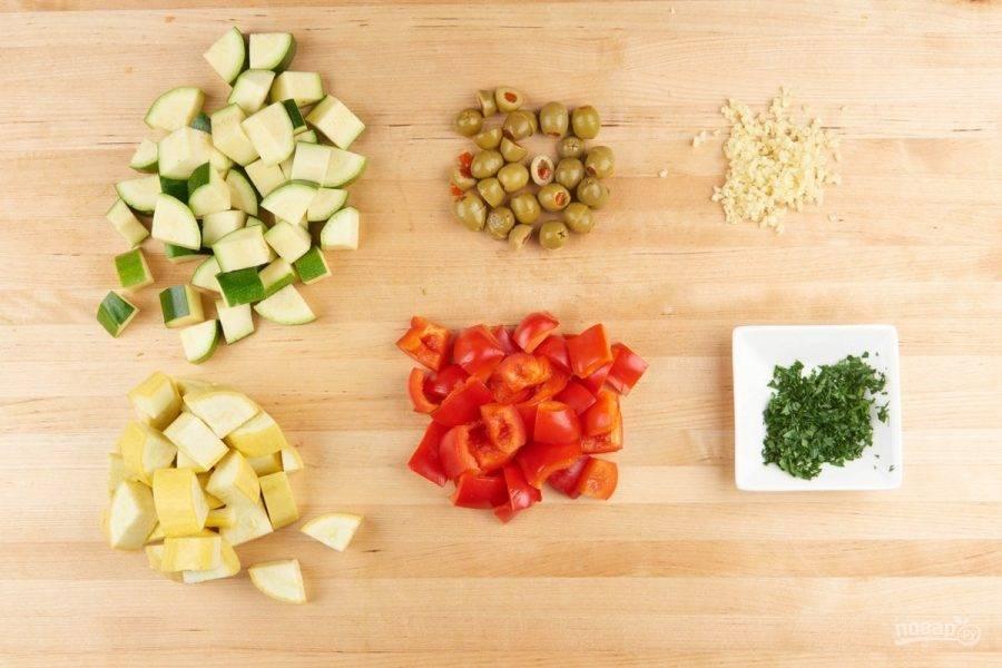 1. Подготовьте овощи. Нарежьте кубиками кабачок, перец и цукини. Мелко нашинкуйте чеснок и петрушку. Разделите на половинки оливки.