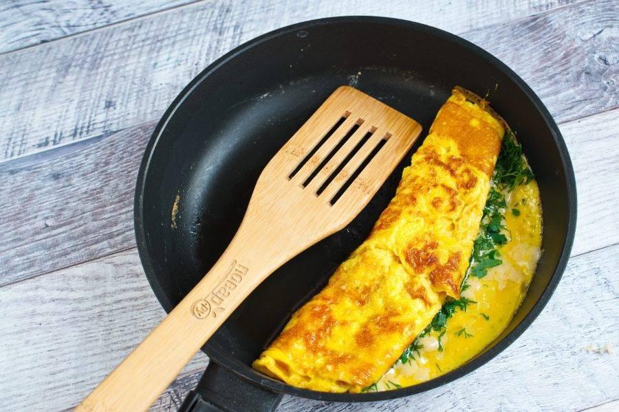 Половину омлета посыпьте тертым сыром и зеленью, накройте второй половиной, готовьте еще пару минут.