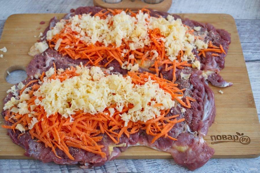Снимите пленку, посыпьте мясо тертыми морковью и сыром.