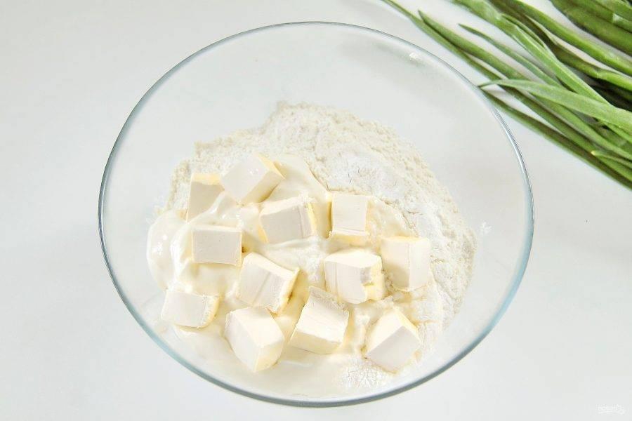 Приготовьте тесто. Для этого в глубокой миске соедините муку, щепотку соли, разрыхлитель, сметану и нарезанный кубиками маргарин.