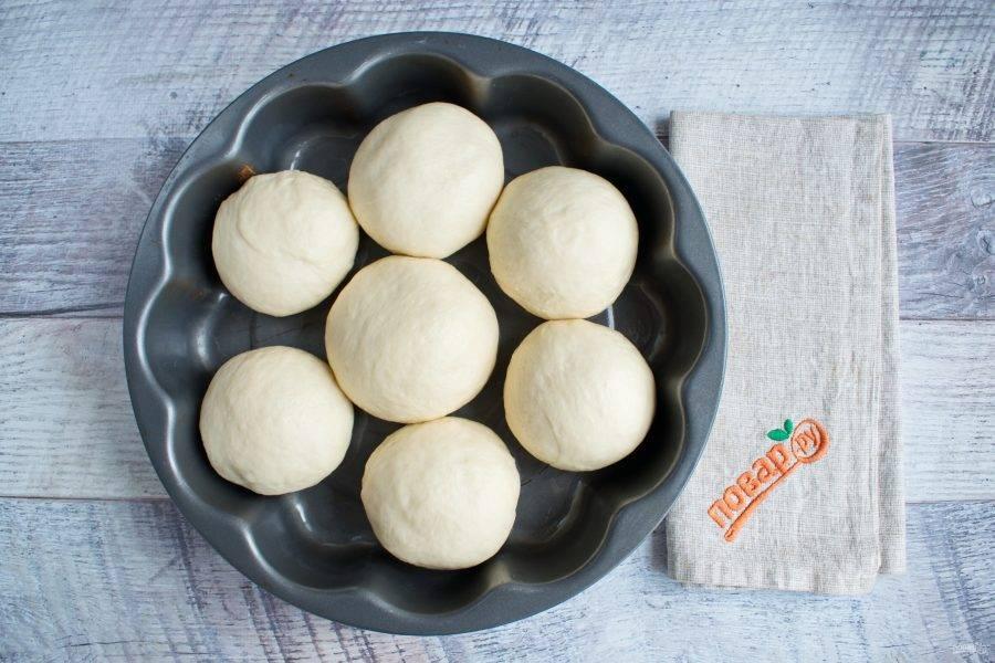 Разделите тесто на 7 равных частей. Каждую примните в круглую лепешку, соберите тесто в центр, переверните и округлите. Круглые заготовки положите в виде цветка в форму (23 см), смазанную маслом. Накройте пищевой пленкой, поставьте в теплое место для подхода на 40 минут.