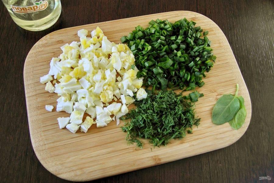 Нарежьте кубиками вареные яйца, зелень измельчите мелко ножом.