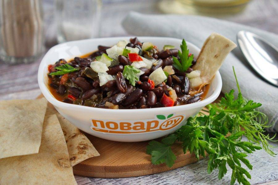 Подавайте суп из черной фасоли со свежим огурцом, зеленью и чипсами из лаваша. Приятного аппетита!