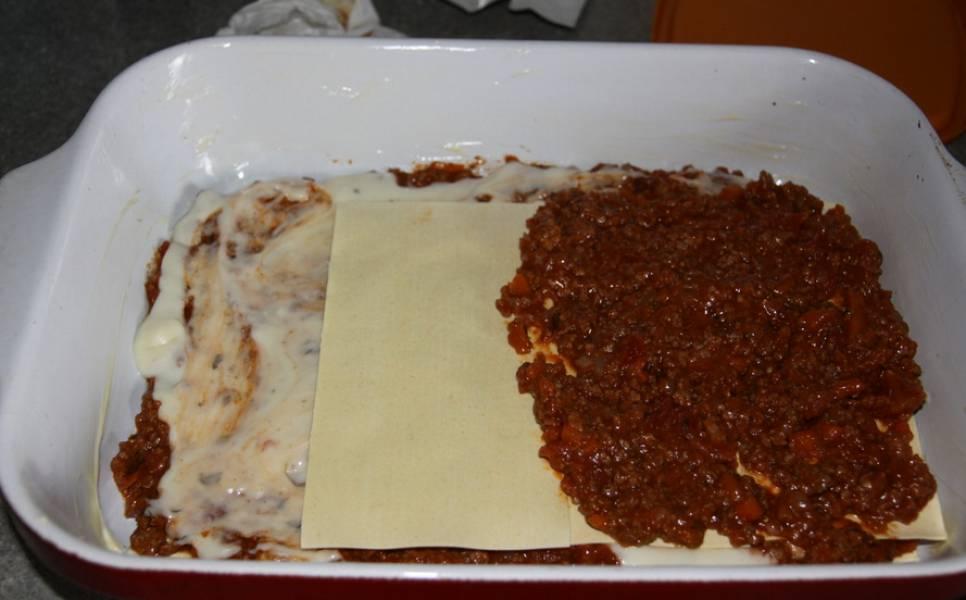"""Смажьте жаропрочную форму сливочным маслом. На дно влейте половник соуса и выложите три листа лазаньи. Сверху распределите часть мясного соуса и соуса """"Бешамель"""". Далее выкладывайте блюдо слоями, постоянно чередуя: листы лазаньи, мясной соус, соус """"Бешамель"""" и тертую моцареллу."""