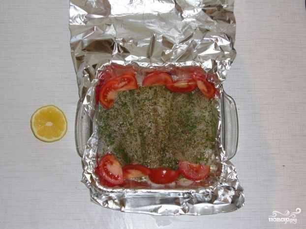 На рыбу выдавливаем сок половины лимона, солим, перчим, приправляем. Вокруг рыбки выкладываем кусочки помидоров.