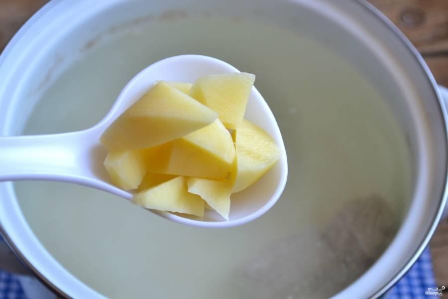 Картофель порежьте на небольшие кусочки и отправьте в кастрюлю.