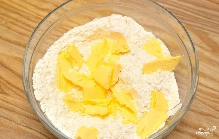 2. Холодное сливочное масло порубите и выложите в муку.