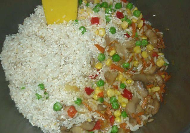 """Измельчаем морковь и лук. Обжариваем их в чаше мультиваки в режиме """"Выпечка"""" 10 минут. Добавляем порезанные пластинками грибы, жарим еще 10 минут, а затем засыпаем овощную смесь и рис."""