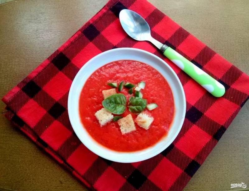 Оливковое масло добавьте в самом конце для сохранения ярко-красного цвета, перемешайте. Разлейте суп в порционные тарелки, выложите сверху измельченный огурец, сухарики и свежий базилик. Приятного аппетита!