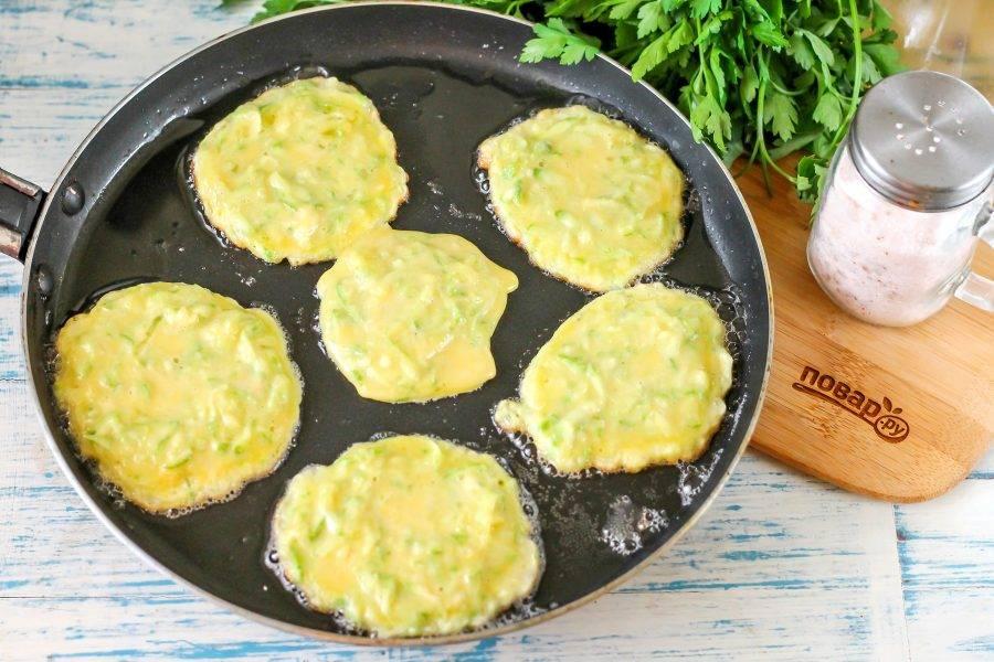 Прогрейте сковороду с растительным маслом, выложите в него столовой ложкой части теста. Обжарьте на умеренном нагреве около минуты, затем переверните на другую сторону.