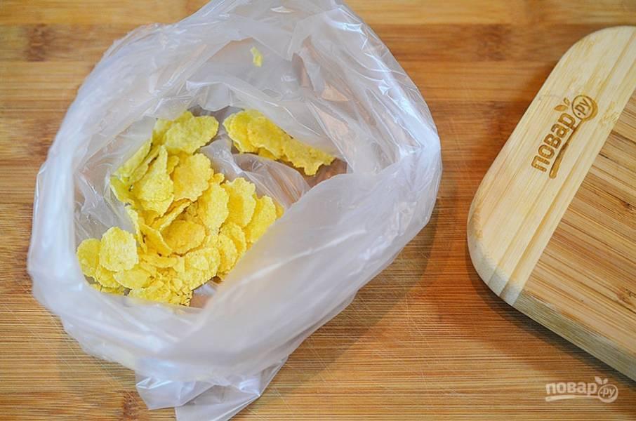 Кукурузные хлопья положите в пакет, затем измельчите или прокатайте скалкой до измельчения.