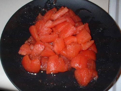 Охлаждаем под проточной водой. Разрезаем пополам помидоры и удаляем семена. Грубо нарезаем.