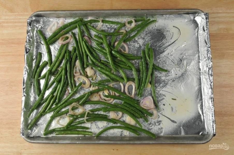 2. После этого выложите фасоль с луком на противень с фольгой. Сверху разложите розмарин, соль, перец и влейте 1 ч. ложку масла. Отправьте овощи запекаться на 5 минут в духовку при 230 градусах.