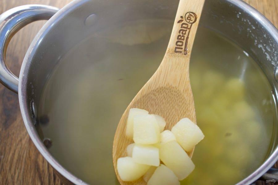 Картофель нарежьте средними кубиками, залейте водой или бульоном, добавьте перец горошком, лавровый лист. Доведите до кипения, варите на среднем огне до мягкости картофеля.