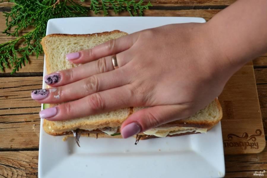 Сверху снова положите кружочки огурца, смажьте майонезом и накройте хлебом. Придавите рукой на несколько минут, чтобы все слои соединились.