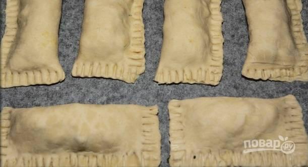 9. Готовые слойки выложите на противень, застеленный пергаментом. При желании можно смазать будущие слойки взбитым желтком. Отправьте в духовку и выпекайте при температуре 180 градусов около 25 минут до румяности.