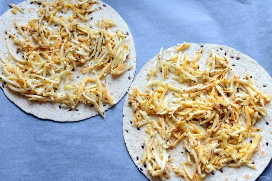 Застелите противень пергаментом и разложите тортильи. Распределите на тортильях сырную смесь и поставьте в духовку.