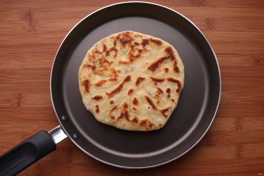Обжарьте хачапури на сухой сковороде, не забывая смазывать тесто, до румяной корочки.