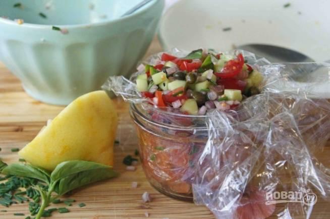 Возьмите цилиндрическую формочку или кулинарное кольцо (формочку лучше устелить целлофаном), уложите вниз рыбу, сверху — овощную смесь.