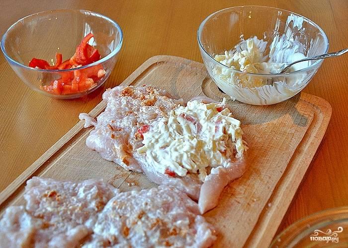 """Для начинки в пиалку с остатками соуса добавьте натертый твердый сыр. Отлично подойдет """"Маасдам"""" или """"Радомер"""". Также добавьте в пиалку очищенный и нарезанный соломкой красный болгарский перец. Получившуюся начинку выложите на куриное филе."""
