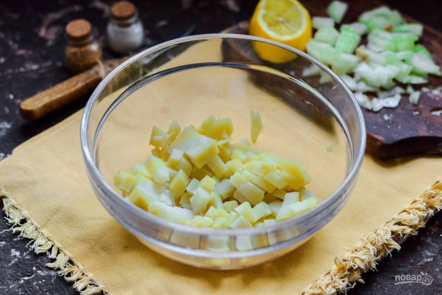 Очистите вареный картофель, нарежьте небольшими кубиками и переложите в салатник.