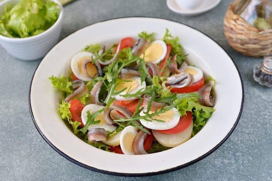 Поверх салата выложите филе анчоуса, все слегка поперчите, сбрызните оливковым маслом. При желании салат можно слегка посолить. Добавьте сверху еще немного рукколы и подавайте к столу.
