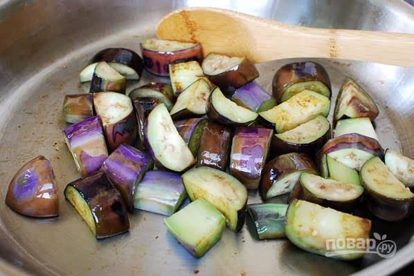 2. Разогрейте на сковороде растительное масло. Выложите баклажаны и обжарьте пару минут до мягкости.